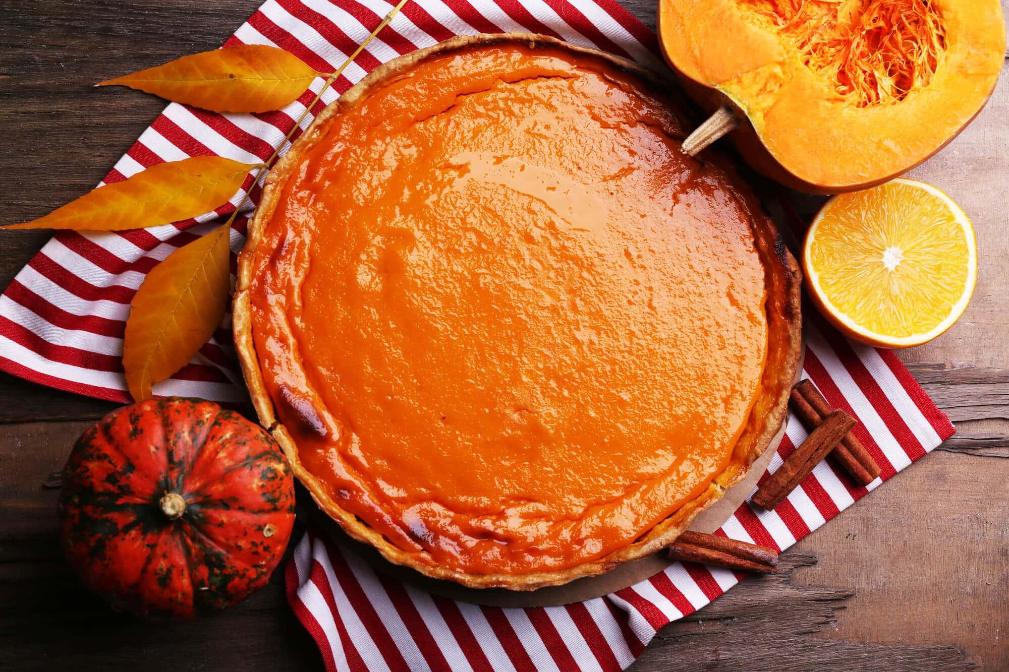 Homemade pumpkin pie on napkin, on wooden background