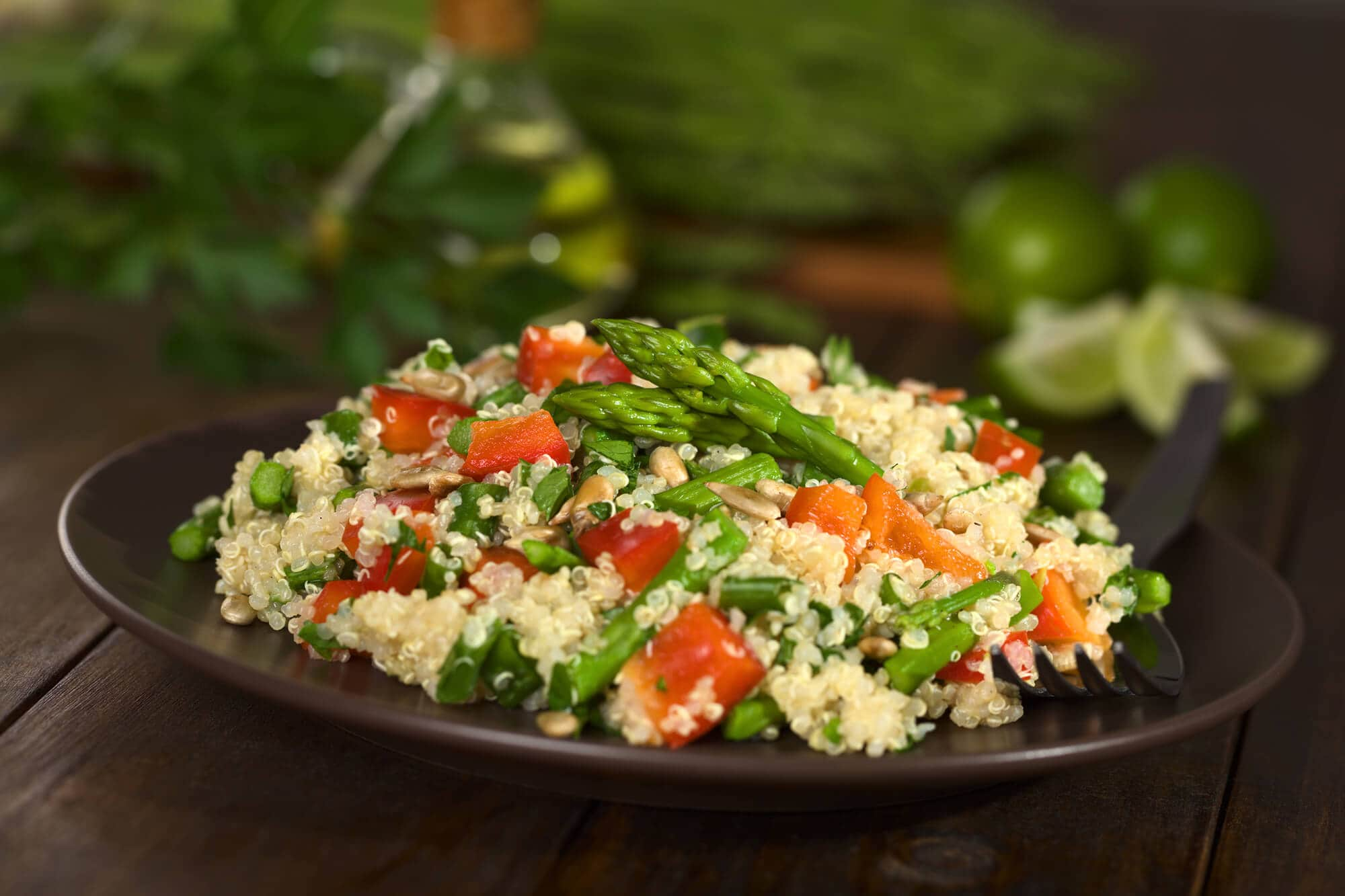 Vegetarian quinoa dish with green asparagus and red bell pepper, sprinkled with parsley and roasted sunflower seeds (Selective Focus, Focus on the asparagus heads on the dish)
