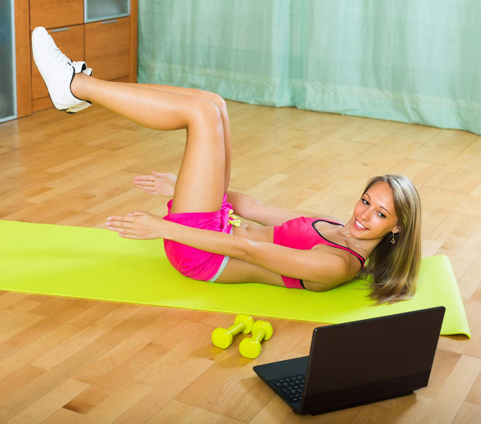 Smiling young woman working out with notebook in gym